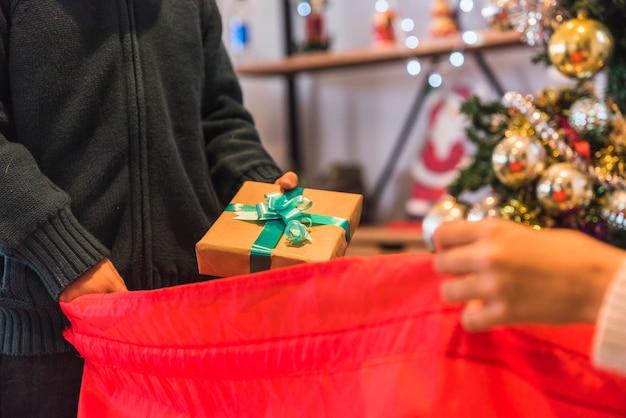 Мальчик принимает подарочную коробку из красного мешка