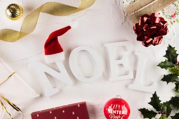 Надпись ноэля возле рождественских украшений