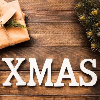 針葉樹の小枝と贈り物の箱の近くのクリスマスの碑文