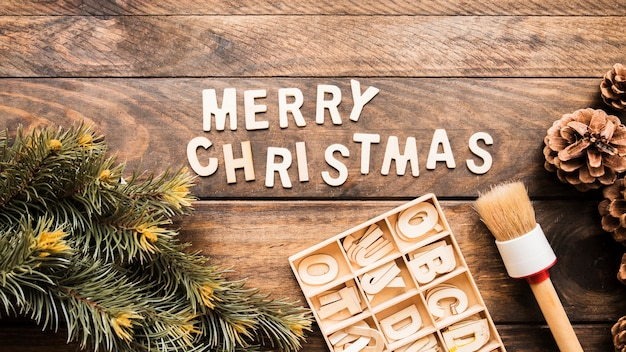 針葉樹の小枝の近くのメリークリスマスの碑文、