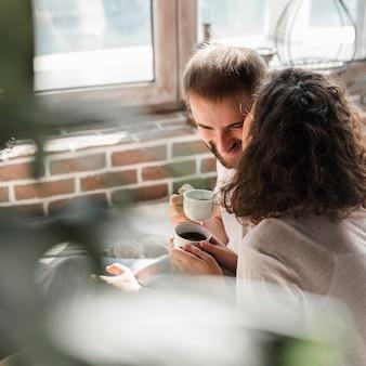 彼女のボーイフレンドにキスしている女性のコーヒー