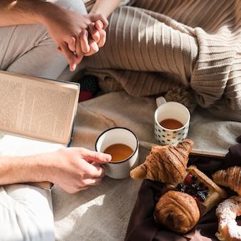 朝食でカップルがお互いの手を握っているの俯瞰
