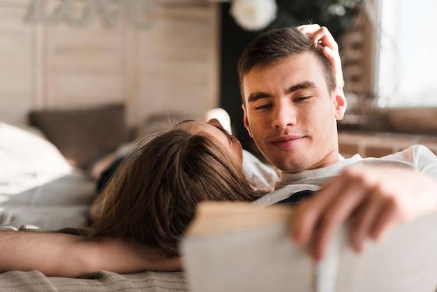 Вид сзади женщины, лежа на кровати возле человека, читая книгу