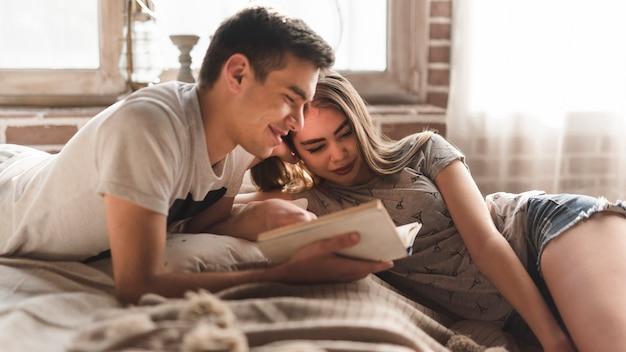 Молодая пара лежит на кровати и смотрит на книгу