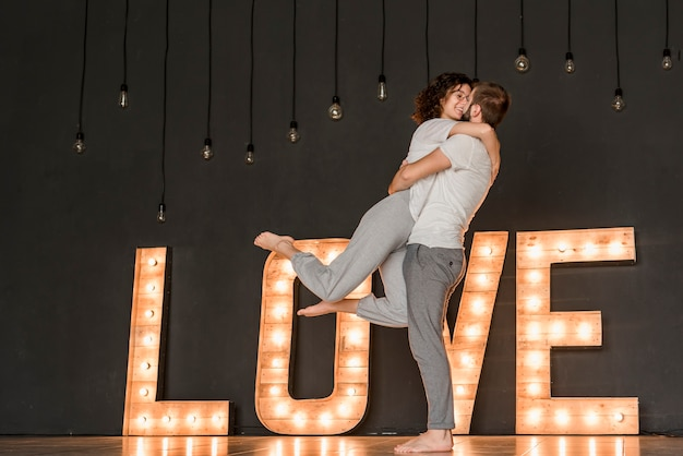 黒い壁に照らされた愛のテキストの前に愛情のあるカップルの立っています。