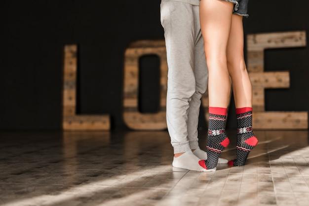 床に靴下立って身に着けているカップルの足にキスのクローズアップ