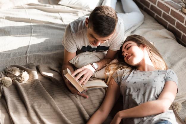 Женщина лежит на кровати и смотрит на книгу