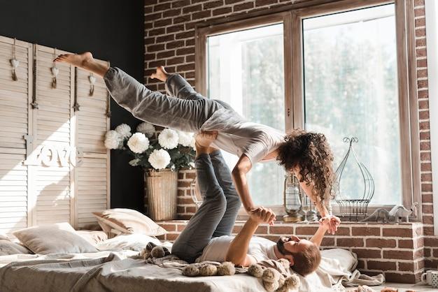 自宅のベッドで男の足のバランスをとる女性のクローズアップ