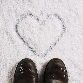 雪の上に描かれた心臓の近くのブーツ