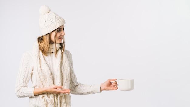 カップと白い服の女