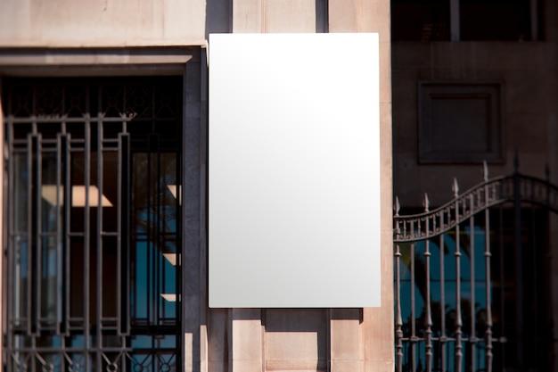 金属門の近くの長方形の白い壁看板