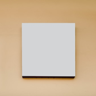 ベージュ色の背景に白い正方形の看板