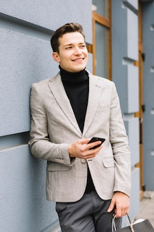 Красивый молодой человек, держа в руке сотовый телефон, глядя