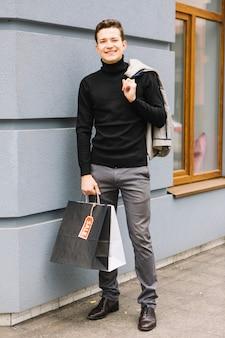 おしゃれな若い男が彼の肩の上にジャケットを持っているショッピングバッグ