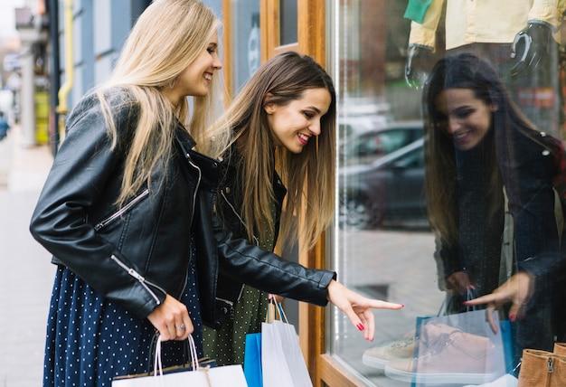 Усмехаясь белокурая молодая женщина смотря ее подругу указывая на ботинки в витрине