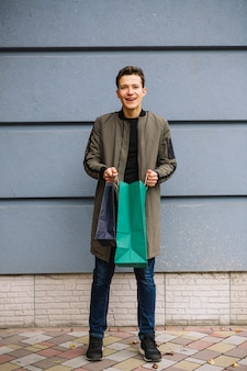 買い物袋を保持している壁に立っている笑顔の若い男