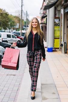 カラフルな買い物袋が付いている通りを歩いて若い女性