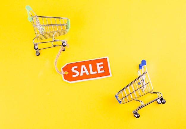 黄色の背景に販売タグ付きミニチュア空っぽのショッピングカート