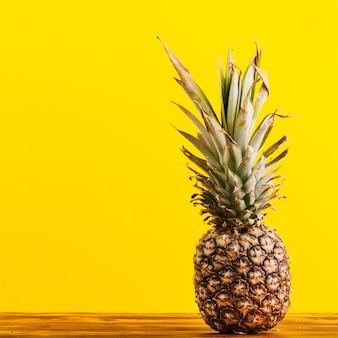 黄色の背景にテーブルの上の全体のパイナップル