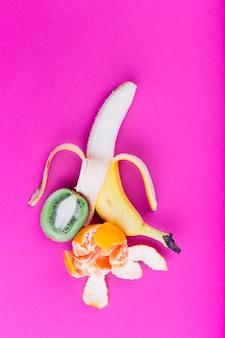 皮をむいたバナナ。ピンクの背景にオレンジと半分のキウイ