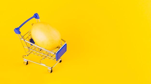 黄色の背景に対してショッピングカート内のレモン