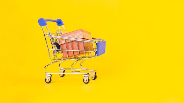 黄色の背景に対してミニチュアショッピングカートのピンクのギフトボックス
