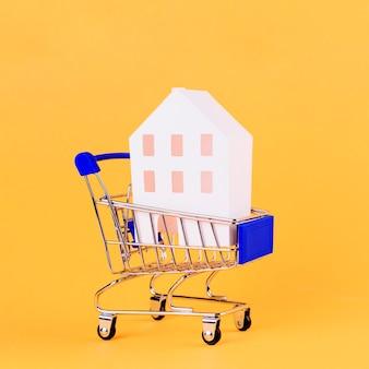 黄色の背景に対してショッピングカート内の家モデル