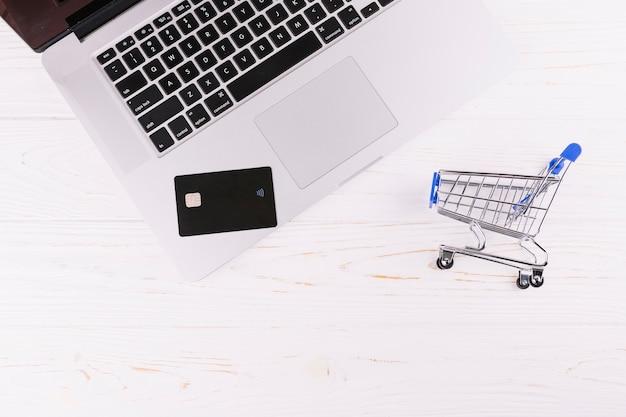 木製の机の上のミニチュアショッピングカートと旅行カードのラップトップ