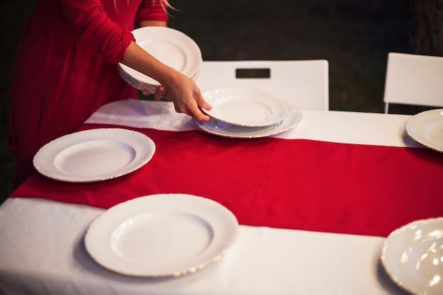 クリスマスディナーのテーブルを設定している若い女性