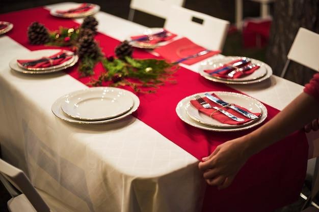 夕食のための赤いテーブルのランナーを固定する手