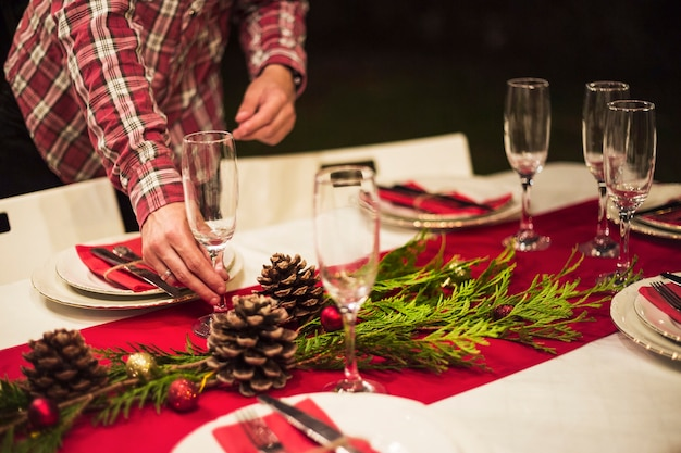 クリスマステーブル上にシャンパングラスを置く手