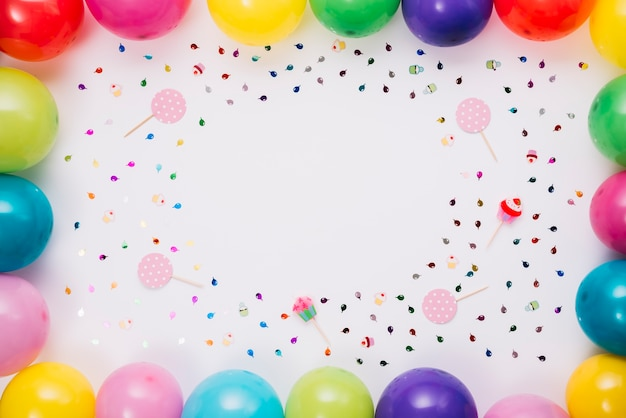 Разноцветные воздушные шары граничат с конфетти и реквизита на белом фоне