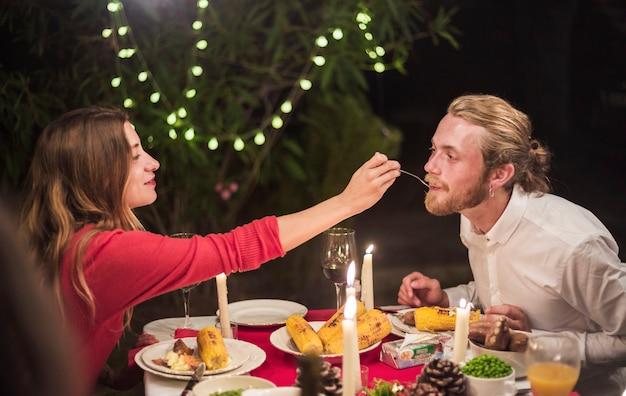 休日の夕食でスプーンで男性を養う女性