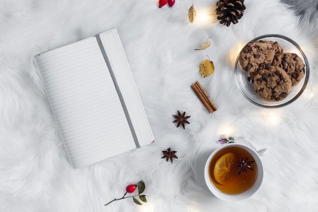 クッキーと紅茶の近くに格子縞のノートを開いた