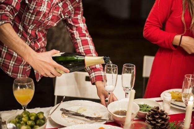 お祝いのテーブルでガラスにシャンパンを注ぐ男