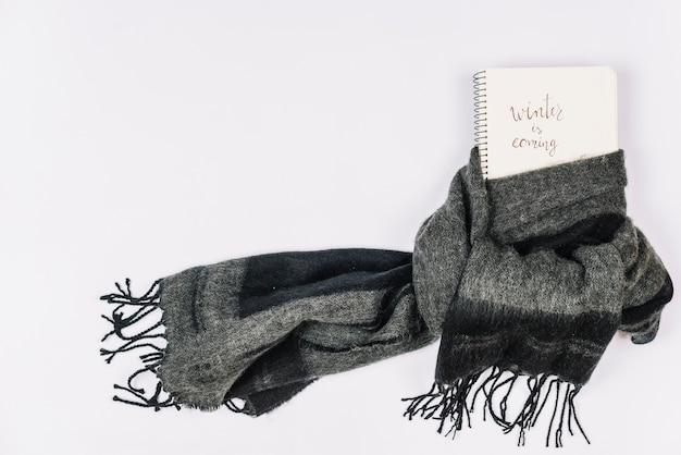 暖かい灰色のスカーフで包まれたノートブック