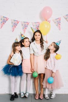 風船とギフトボックスを手に保持している白いレンガの壁に立っている女の子のグループ