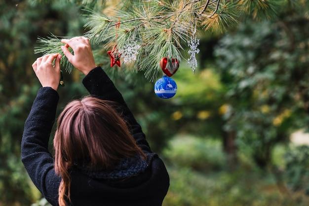 森林の小枝にクリスマスのおもちゃを吊るしている女性