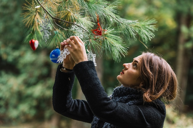 森林の小枝にクリスマスのおもちゃを吊るす若い女性