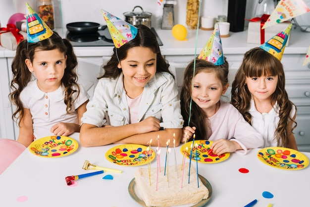 誕生日ケーキを待っているテーブルの上の誕生日紙プレートを頭の上のパーティー帽子をかぶっている女の子