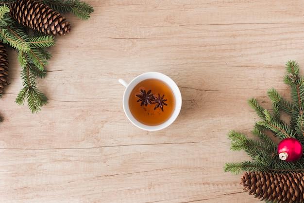 針葉樹の小枝と枝の間の飲み物のカップ