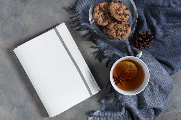ノートパソコンで青い格子縞の上にビスケットと紅茶