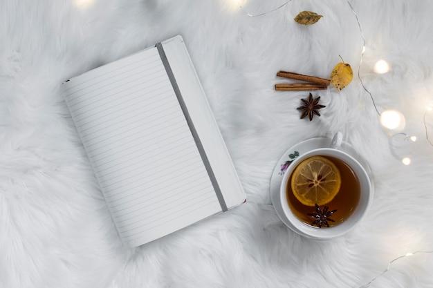 ふわふわの白いチェック柄のノートパソコン付きレモンティー