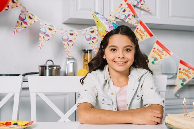 カメラ目線の頭の上のパーティーハットを着て笑顔の誕生日の女の子の肖像画