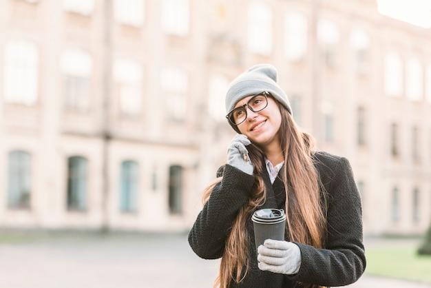 スマートフォンで通りに話すカップを持つ若い笑顔の女性