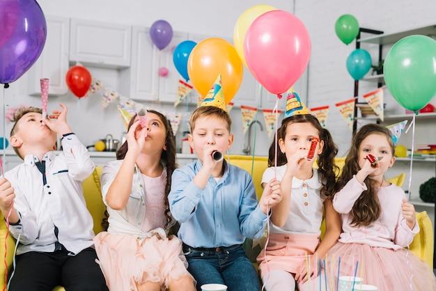 カラフルな風船を押しながらパーティーの誕生日にホーンを吹く子供たち