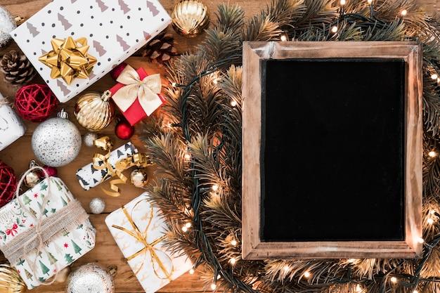 クリスマスの装飾の近くの妖精の光の間のモミの小枝のフォトフレーム