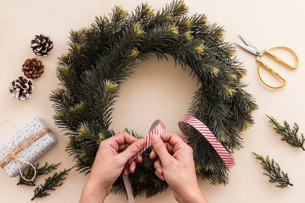 リボンでクリスマスの花輪を飾る人