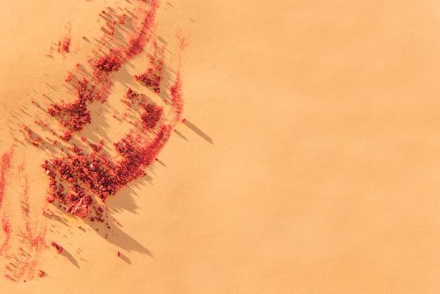 色付きの背景に砕いた化粧品フェイスパウダーの俯瞰