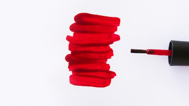Высокий угол обзора красных мазков лака для ногтей и кисти на белом фоне